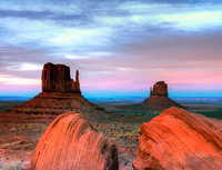 Pink and blue colors highlight a sunset in Monument Valley with Ansel Adams rocks in the foreground