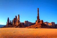 The desert sand ripples form the wind as the Totem Pole rises up to the sky.